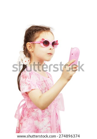 Little pretty girl with pink sunglasses holds toy mobile - stock photo