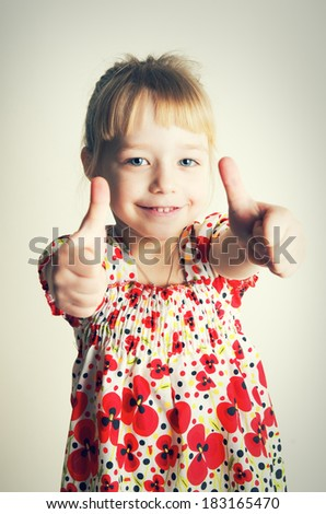 Little pretty girl with thumb up isolated on white background. Ok sign by child.