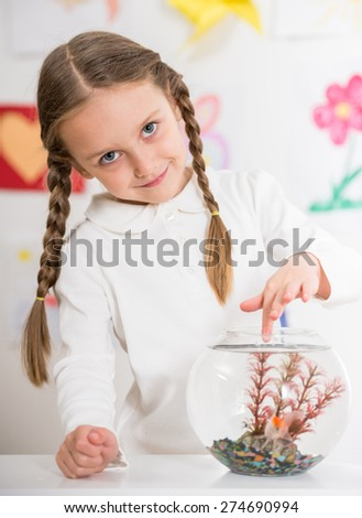 Little pretty  smiling girl in white  pullover  playing with gold fish in aquarium on colorful background. - stock photo