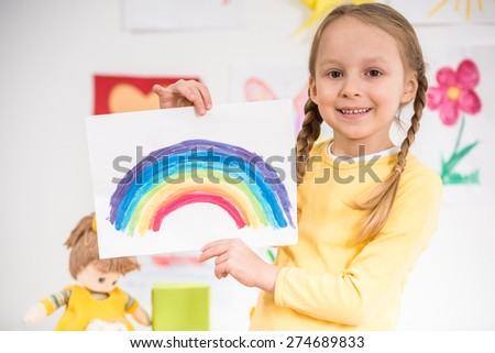 Little pretty smiling girl in yellow  pullover  holding a picture of rainbow on colorful background.