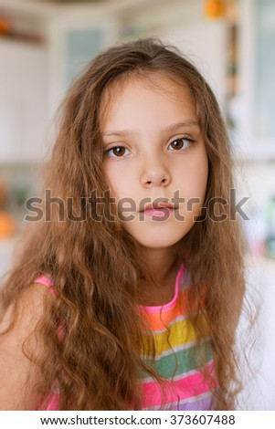 Little pretty thoughtful girl on the background of the kitchen. - stock photo