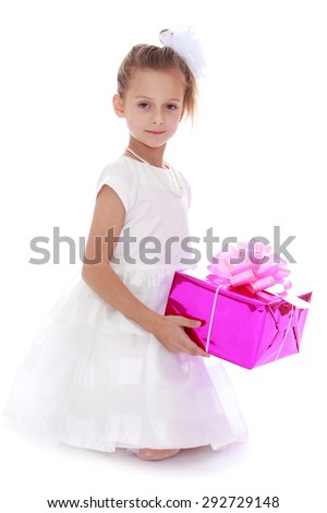 Little Princess.Beautiful little girl in a white long party dress, holding a pink gift-wrapped box with a gift , a girl stands on her knees - isolated on white background