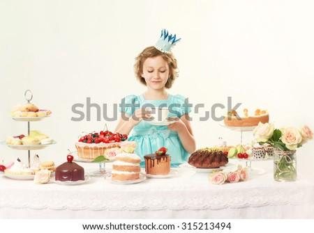 Little princess in elegant blue dress, drinking tea. Birthday party. Indoor - stock photo