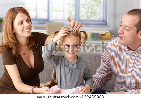 Little princess in tiara at home with father and pregnant mother. - stock photo