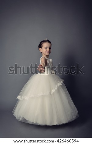 Little Princess posing in evening dress. Little girl dancing ballet in studio over gray background. - stock photo