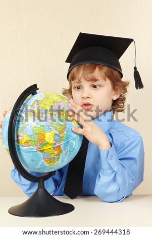 Little professor in academic hat looks at a globe  - stock photo