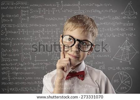 little pupil solves math problem - stock photo