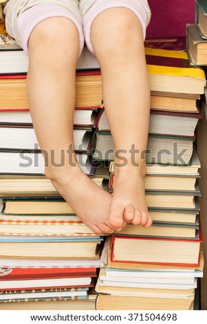 Little reader and many old books standing stacks. Education or library concept - stock photo