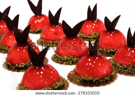 Little red cakes decorated with chocolate leaves - stock photo