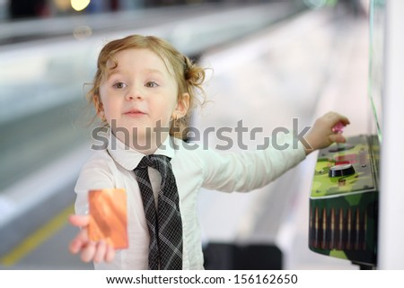 Little red hair girl in white shirt and tie plays on game machine and shows credit card.