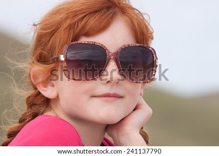 little red haired girl in over sized sunglasses  - stock photo