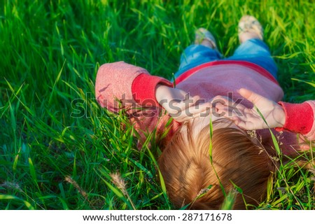 little red-haired girl lying on back on green grass and closes his eyes from the sun - stock photo