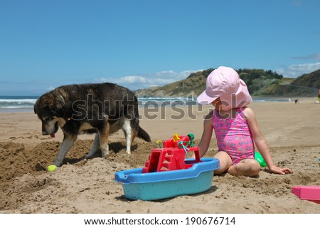 little red headed girl in pink bathing suit on beach making sand castles with her pet dog digging at its ball nearby - stock photo