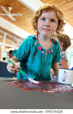 little red headed girl painting a picture during her preschool kindergarten class - stock photo