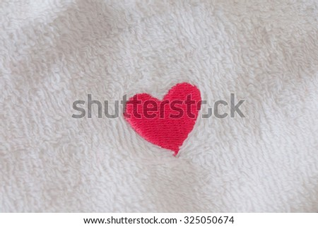 little red heart on white towel - textile background
