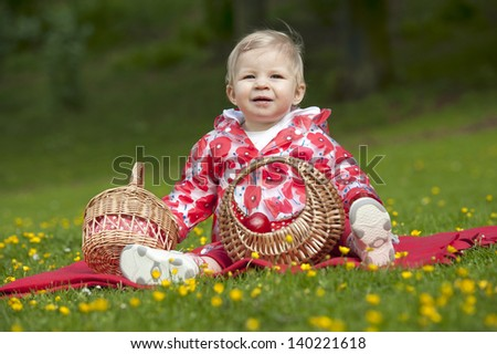 little red hood toddler seated in grass with buttercups