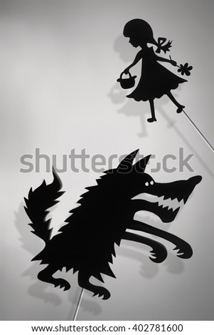 Little Red Riding Hood and the Big Bad Wolf shadow puppets and their shades. Copy space background. - stock photo