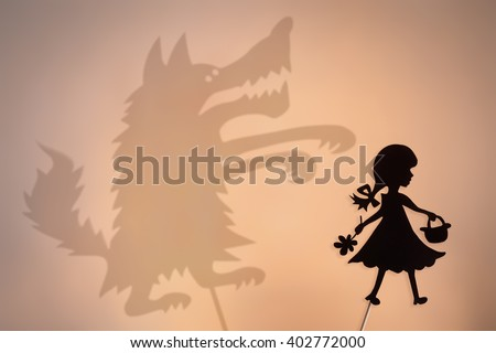 Little Red Riding Hood shadow puppet and the Big Bad Wolf's shade with the soft glowing screen of shadow theater in the background. - stock photo
