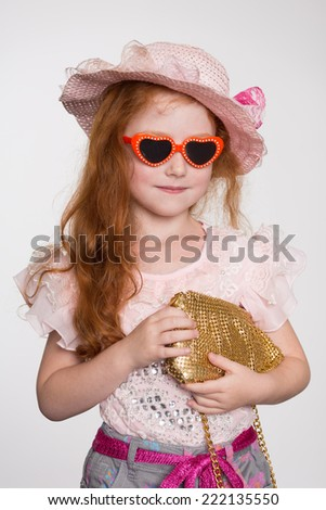 Little redhead fashionista in a sunglasses and hat. Girl is six years. - stock photo