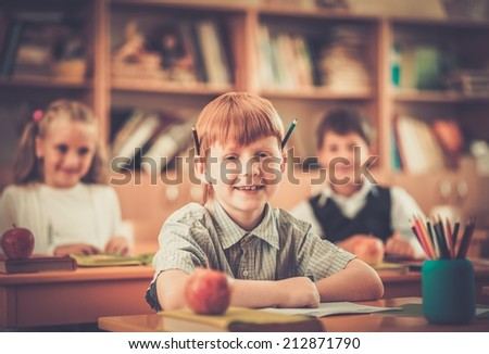 Little redhead schoolboy behind school desk during lesson