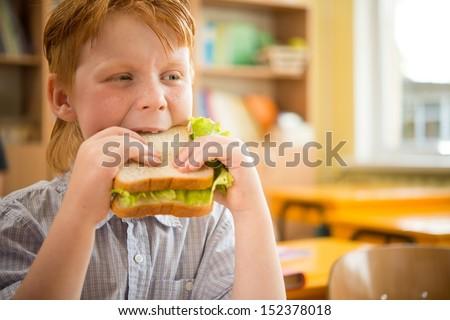 Little redhead schoolboy eating sandwich in class - stock photo