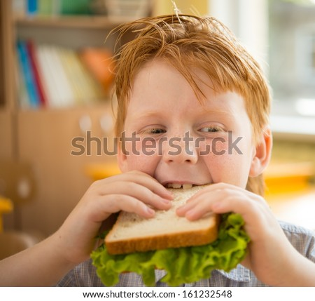 Little redhead schoolboy eating sandwich in class - stock photo