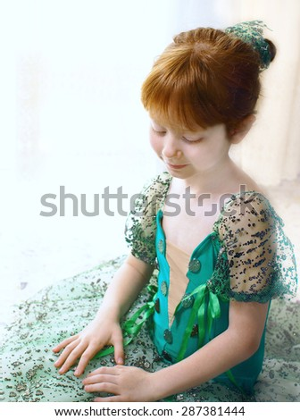 Little redheaded girl wearing green trimmed costume of ballet dancer for a performance and sitting on the floor, selective focus - stock photo