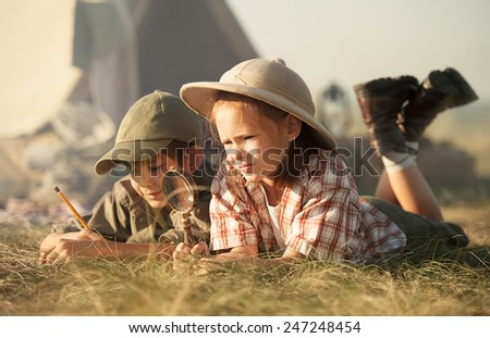 Little researchers - boy and girl - study of insects and plants, crawling on his stomach on the grass in a sunny summer day - stock photo