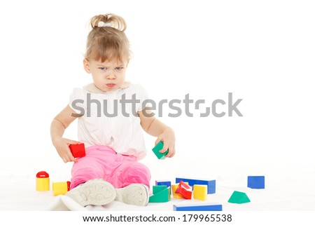 Little resentful girl plays with children blocks set on a white background. Learning toys and early development. - stock photo