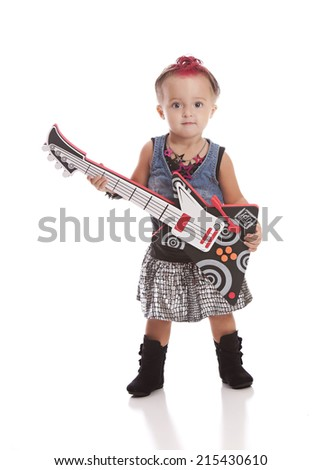 Little Rock Star.  Adorable toddler dressed as a rock star and playing with a toy guitar.  Isolated on white. - stock photo