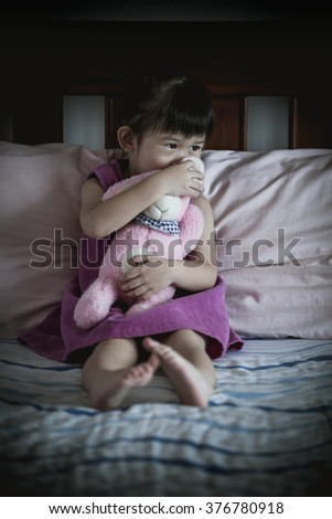 Little sad asian girl sitting on bed with doll in dark bedroom. Vignette picture style. - stock photo
