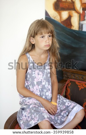 little sad girl with brown eyes sitting on chair - stock photo