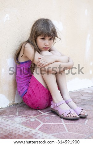 little sad girl with long hair sitting hugging her knees, leaning against the wall - stock photo