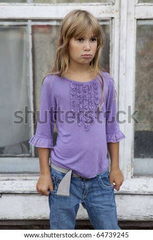 little sad girl with long hair wearing jeans standing at old window - stock photo