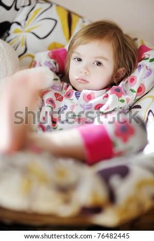 Little sad toddler girl in pajamas on sunny morning - stock photo