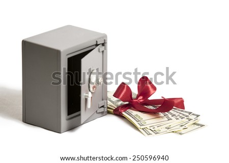 Little safe with red ribbon and stack of money - stock photo