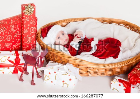 little santa baby with christmas hat lying in basket