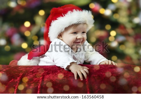 little santa baby with christmas hat lying on her belly
