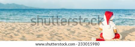 Little Santa boy on the beach. Tropical Christmas - stock photo