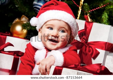 Little Santa boy with gift boxes. - stock photo