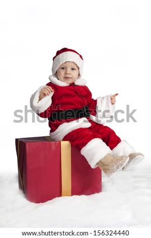 little santa claus seated on a christmas present in the snow - stock photo