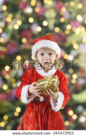 Little santa girl with present in front of a xmas tree