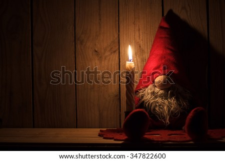 Little Santa gnome is sitting on a wooden shelf with a candle. Christmas mystic fairy tale background - stock photo