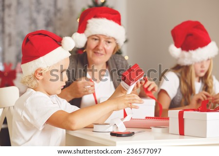 Little Santa Helper. Cute little boy with his family wrapping Christmas gift at home with decorated Christmas Tree and chimney at background
