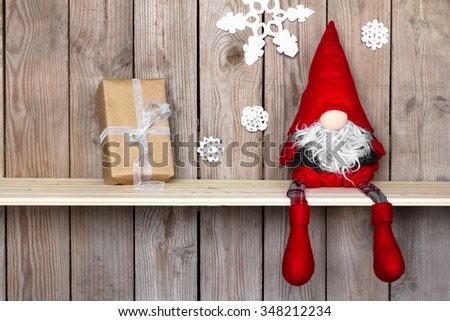 Little Santa helper gnome with Christmas holiday present is sitting on a wooden shelf and waiting for children. Vintage New Year interior - stock photo