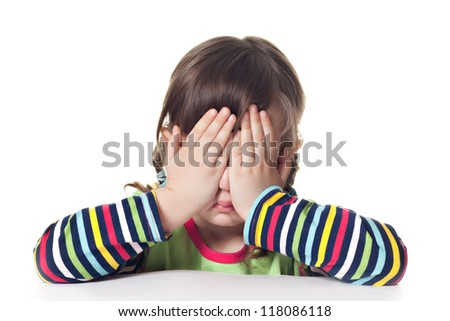 Little scared girl hiding face isolated on white - stock photo