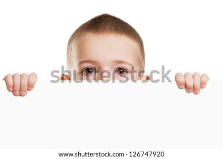 Little scared or worried child boy holding blank white sign or placard hiding face - stock photo