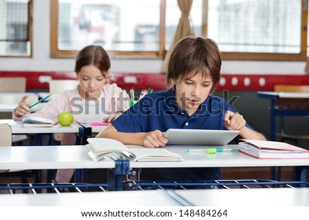 Little school boy using digital tablet with girl studying in background at classroom - stock photo