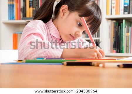 Little school girl wearing an overall doing homework - stock photo