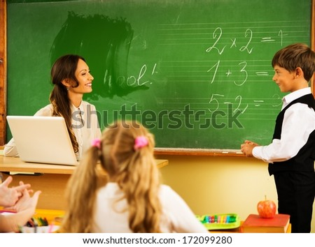 Little schoolboy answering near blackboard in school - stock photo